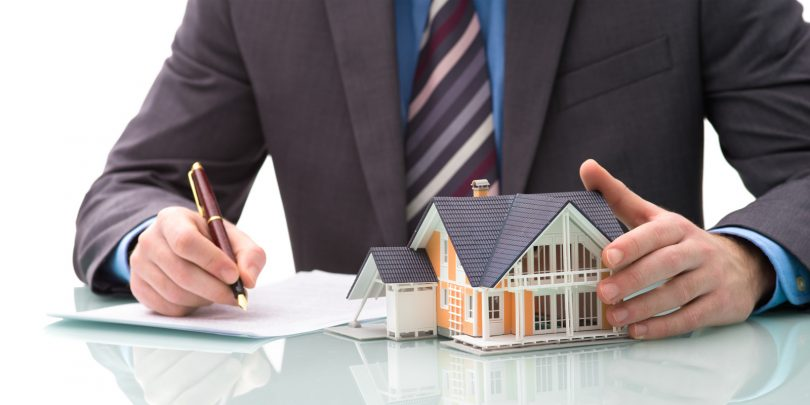 homme d'affaires avec une maison assurance emprunteur